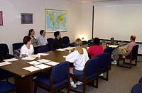 Image of a students sitting around a conference table, papers spread out in front of them