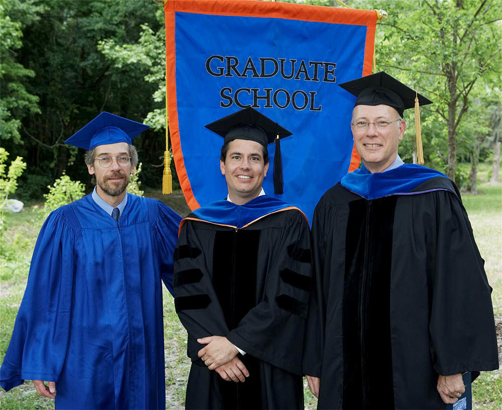"Left to right, Dr. Allred, Dr. Bonilla, and Dr. Dame in University of Florida Regalia, standing in front of a banner that reads ""Graduate School"""