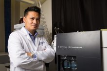 Dr. Rhoel Dinglasan is shown in his laboratory in December 2016 standing in front of a time-of-flight mass spectrometer.